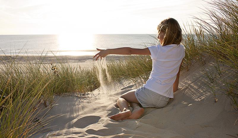 Mädchen sitzt am Strand, Hvidbjerg Strand Feriepark
